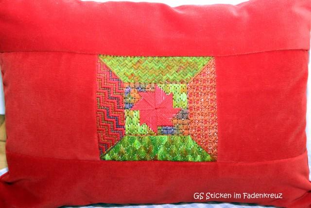 ein etwas anderes Muster - in rot-grün gestickt und auf einem roten Kissen platziert